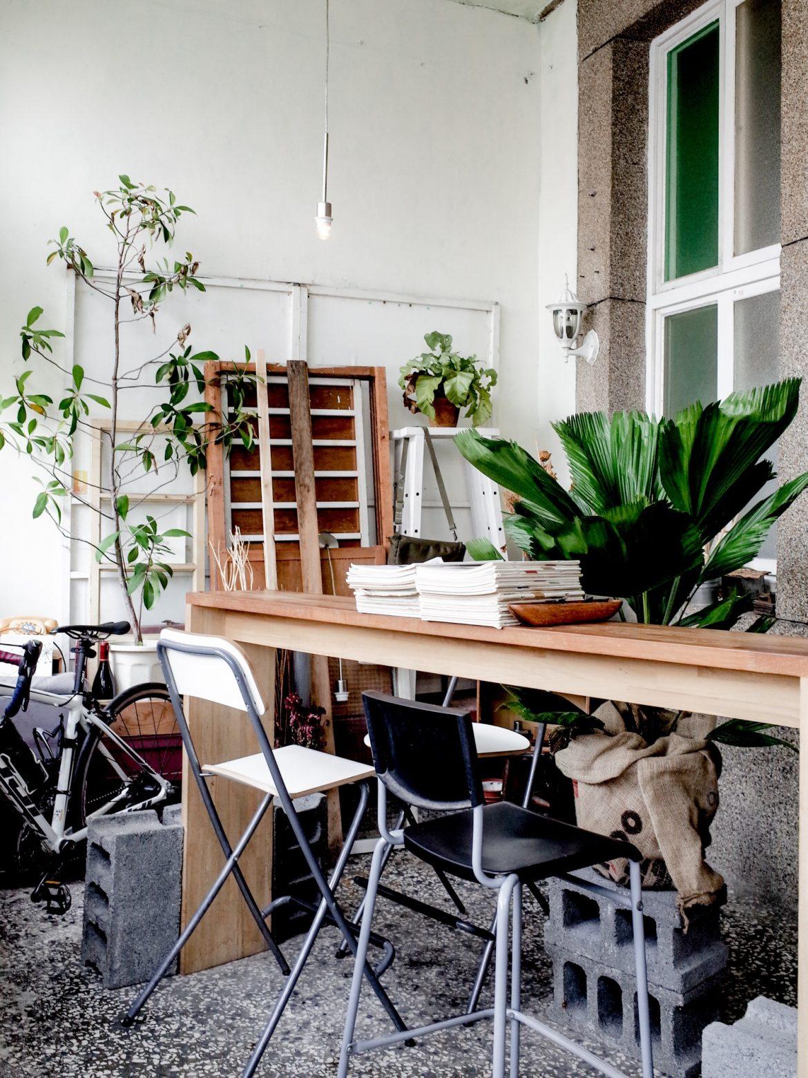 前院的小小座檯,一旁堆疊著木窗與工具,在大量綠色植栽環繞下,竟也有種庭院工作室般的舒適感。