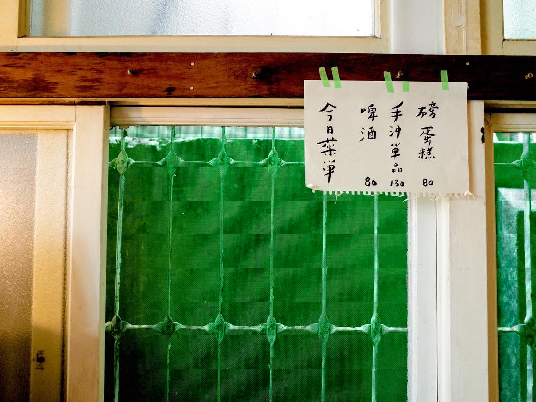 手寫菜單以綠色紙膠帶隨性貼黏在窗框,老舊的綠色紗窗成了最古早味的背景。
